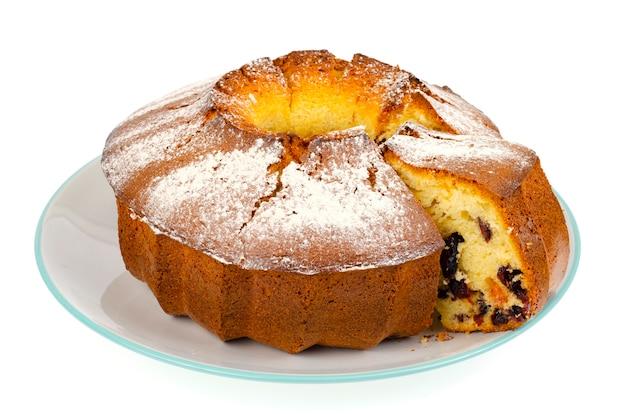 Zelfgemaakte muffin met gedroogde bessen en poedersuiker op plaat.