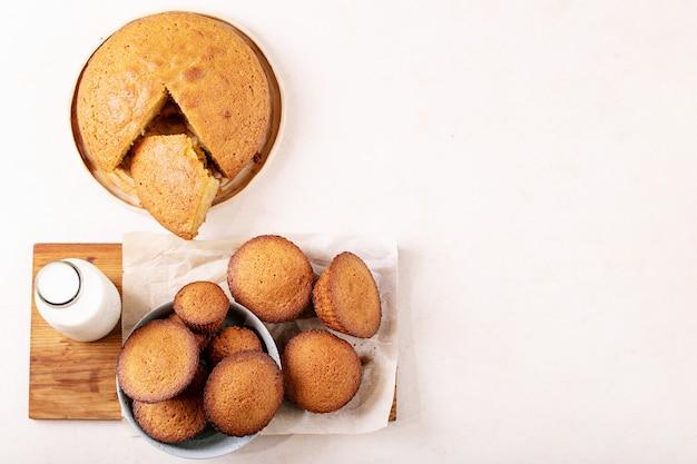 Zelfgemaakte muffins geserveerd met melk in een fles op witte textuur achtergrond. bovenkant, plat gelegd. kopieer ruimte