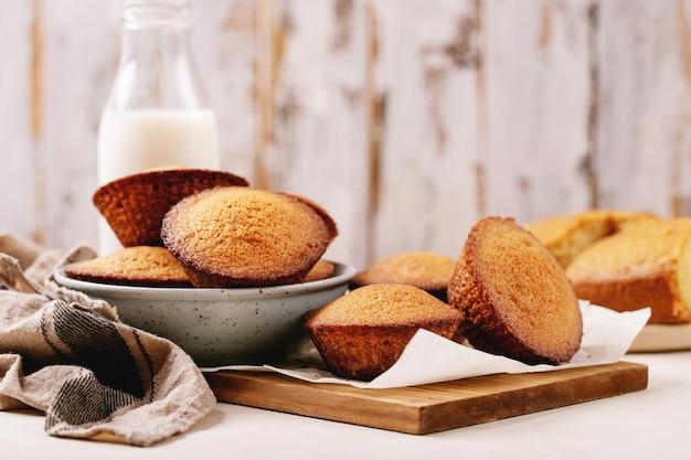 Zelfgemaakte muffins geserveerd met melk in een fles op witte textuur achtergrond