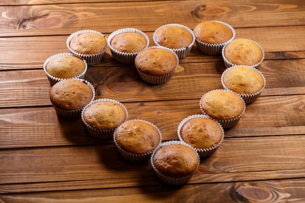 Zelfgemaakte muffins in papieren folie op houten plank