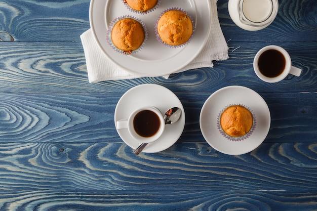 Zelfgemaakte muffins met chocolade chips en bosbessen met een glas melk en koffie. cupcake met chocolade.