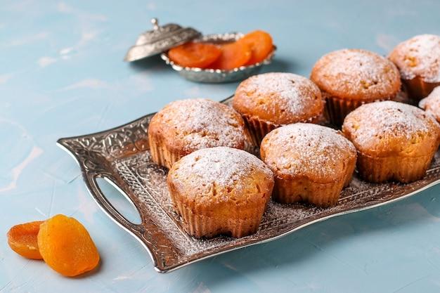 Zelfgemaakte muffins met gedroogde abrikozen bestrooid met poedersuiker op een metalen bakje op een lichtblauw