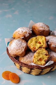 Zelfgemaakte muffins met gedroogde abrikozen bestrooid met poedersuiker op lichtblauw