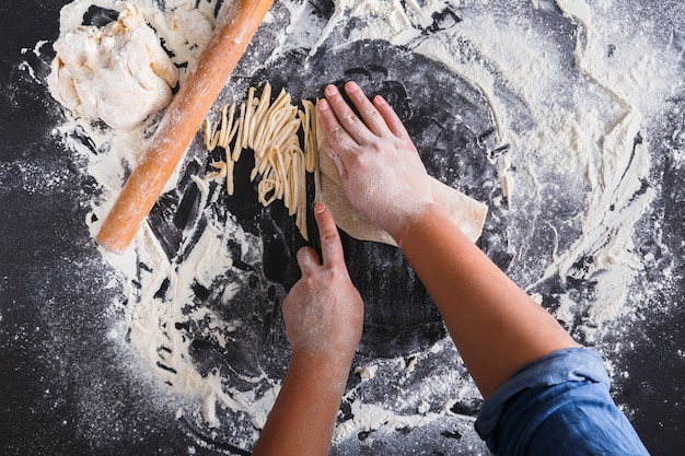 Zelfgemaakte noedels maken, bestrooid tarwemeel en kookhanden. bovenaanzicht op bord of tafel.