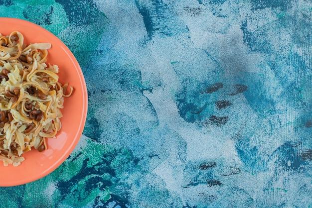 Zelfgemaakte noedels met bonen op een bord op onderzetter, op de blauwe tafel.