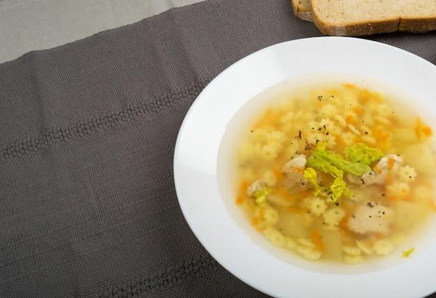 Zelfgemaakte noedelsoep met stukjes kip en groenten. heldere soep met star stelle pasta of stellini pasta