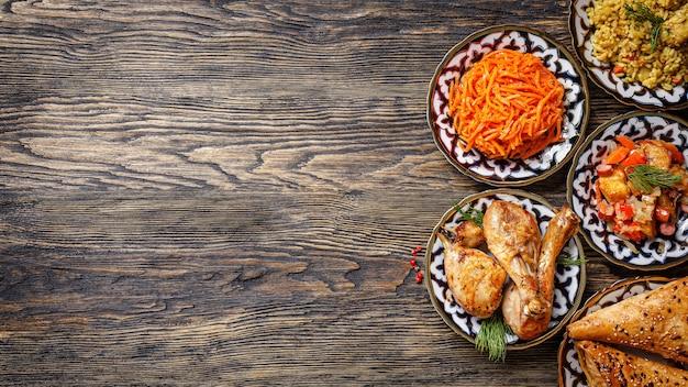 Zelfgemaakte oezbeekse gerechten, pilaf, kip, samsa, koreaanse wortelsalade