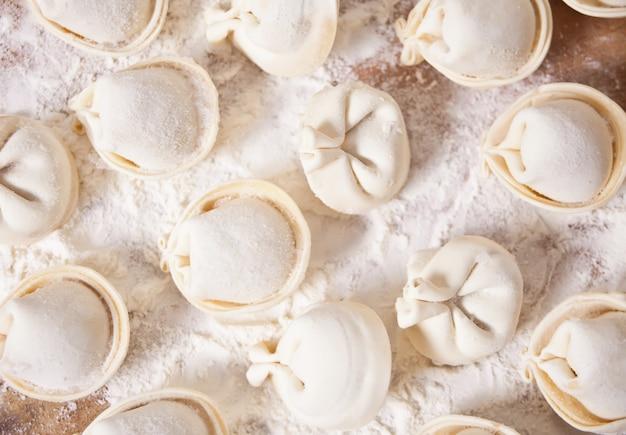 Zelfgemaakte ongekookt russische pelmeni vlees dumplings italiaanse ravioli op snijplank.