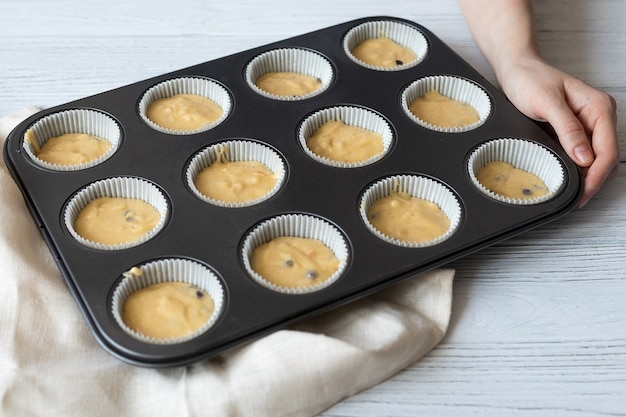 Zelfgemaakte ongekookte muffins, zelfgemaakte gebakken goederen in de vorm op tafel