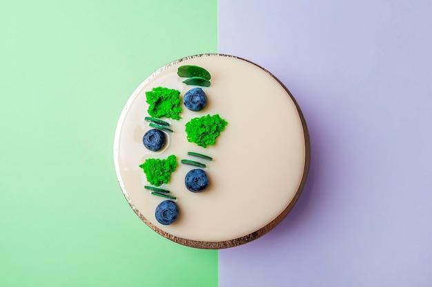 Zelfgemaakte ongesneden veganistische bosbessencake versierd met witte glazuur, room en verse bessen.