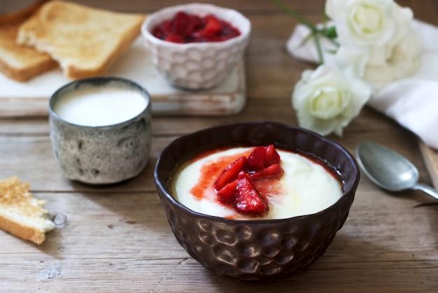 Zelfgemaakte ontbijt van griesmeel pap, aardbeiensaus, koffie met melk en toast op een houten oppervlak.
