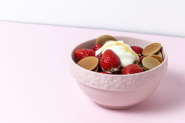 Zelfgemaakte ontbijtgranen mini pannenkoek met yoghurt, honing en aardbeien op kleurrijke tafel.