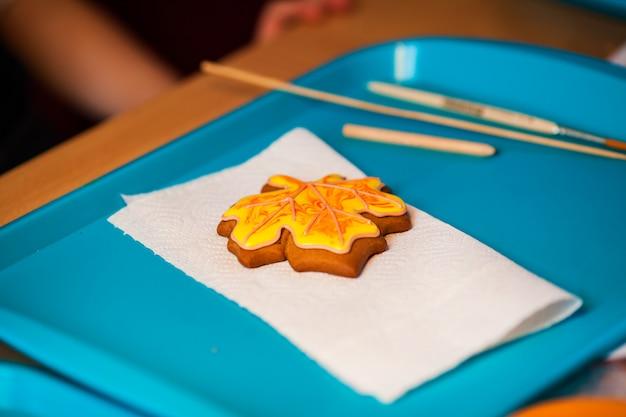 Zelfgemaakte ontbijtkoek koekjes in de vorm van pompoenen voor halloween. herfst esdoorn bladeren op oude houten achtergrond