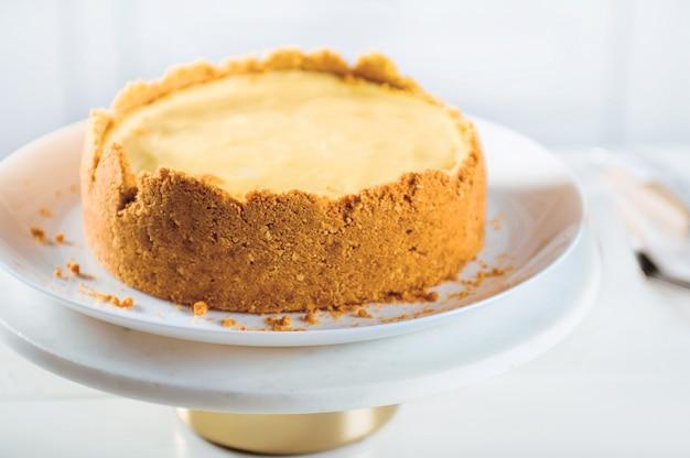 Zelfgemaakte oranje cheesecake op de standaard op een witte ondergrond