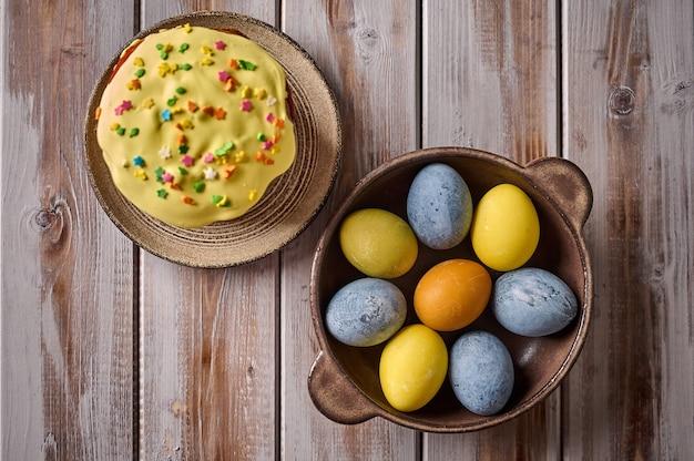 Zelfgemaakte paascake en veelkleurige beschilderde eieren op zwarte schotel
