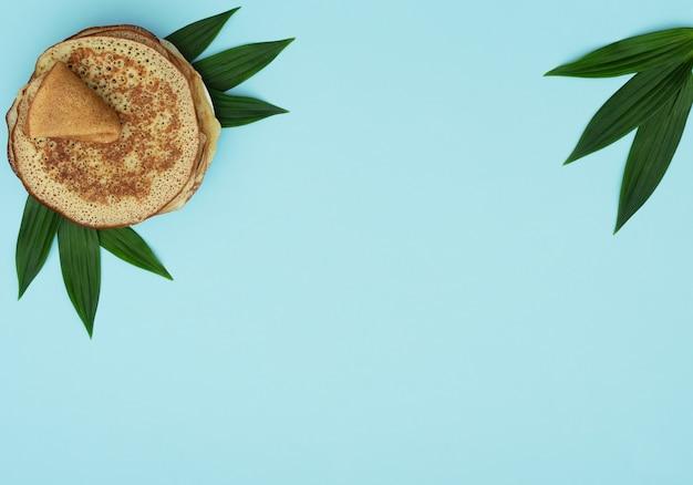 Zelfgemaakte pannekoeken op blauw met groene bladeren