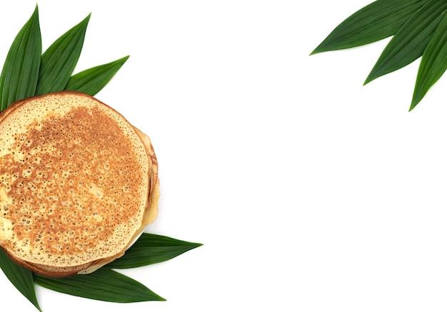Zelfgemaakte pannekoeken op wit met groene bladeren