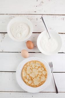 Zelfgemaakte pannenkoeken en ingrediënten op houten tafel