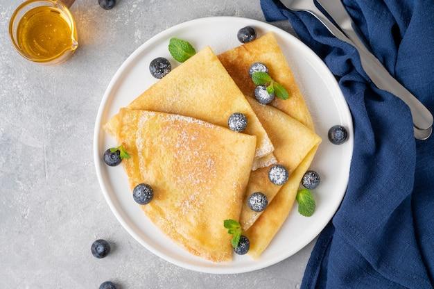 Zelfgemaakte pannenkoeken geserveerd met verse bosbessen en poedersuiker op een witte plaat op een grijze betonnen achtergrond. voedsel voor maslenitsa. kopieer ruimte.
