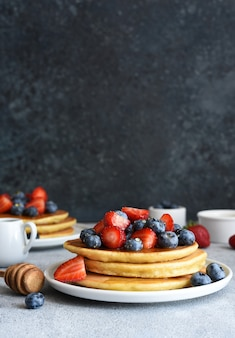 Zelfgemaakte pannenkoeken met aardbeien en bosbessen voor het ontbijt op de keukentafel.