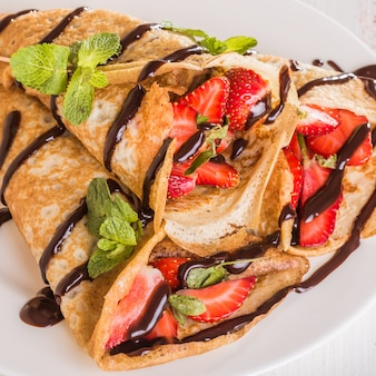 Zelfgemaakte pannenkoeken met aardbeien en chocoladesiroop