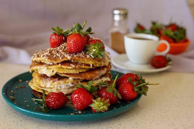 Zelfgemaakte pannenkoeken met aardbeien en honing