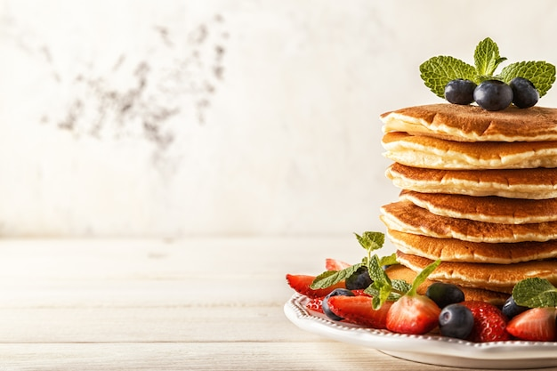 Zelfgemaakte pannenkoeken met bessen en fruit op een witte ondergrond