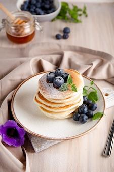 Zelfgemaakte pannenkoeken met bosbessen en poedersuiker op de verticale foto van de witte tafel.