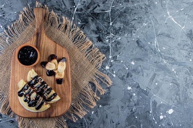 Zelfgemaakte pannenkoeken met chocolade en gesneden banaan op een houten bord.