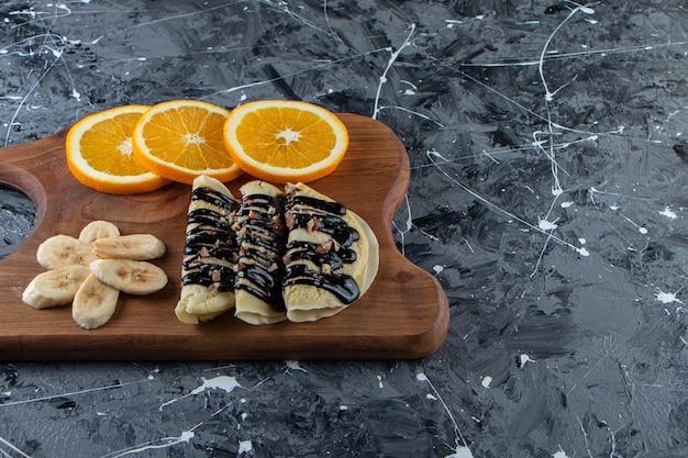 Zelfgemaakte pannenkoeken met chocolade, gesneden banaan en sinaasappel op een houten bord.