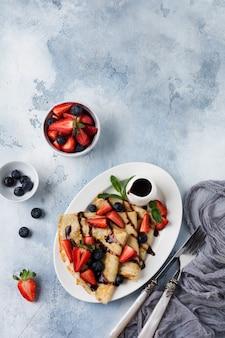 Zelfgemaakte pannenkoeken met chocoladesaus, verse aardbeien en honing voor het ontbijt in mooie witte keramische plaat. ruimte voor tekst of recept. bovenaanzicht