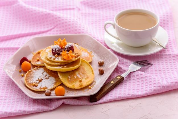 Zelfgemaakte pannenkoeken met frambozen, physalis, poedersuiker op roze servet met kopje thee of koffie