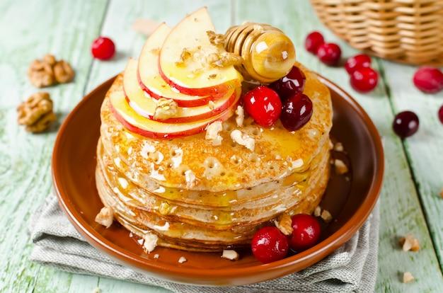 Zelfgemaakte pannenkoeken met honing, appel, veenbessen en noten