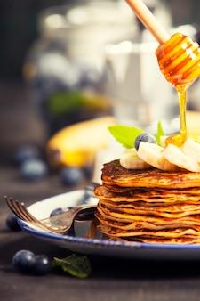 Zelfgemaakte pannenkoeken met verse bananen, bosbessen en honing