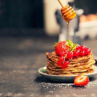 Zelfgemaakte pannenkoeken met verse bessen en honing