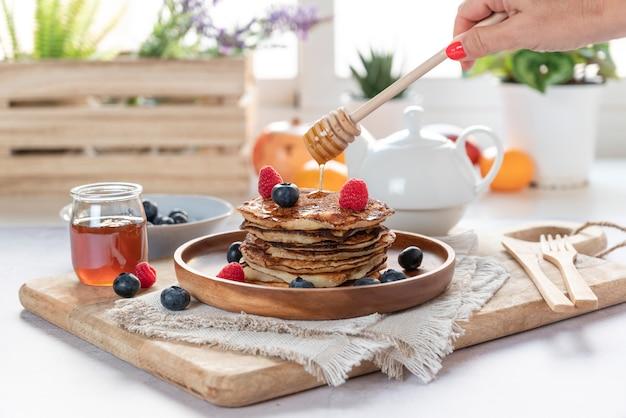 Zelfgemaakte pannenkoeken met verse bosbessen, frambozen en honing. vrouwelijke hand gieten honing