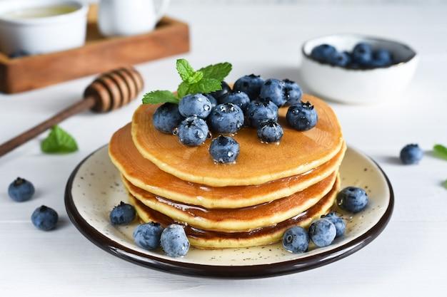Zelfgemaakte pannenkoeken op een witte plaat met honing en bosbessen voor het ontbijt. goedemorgen!