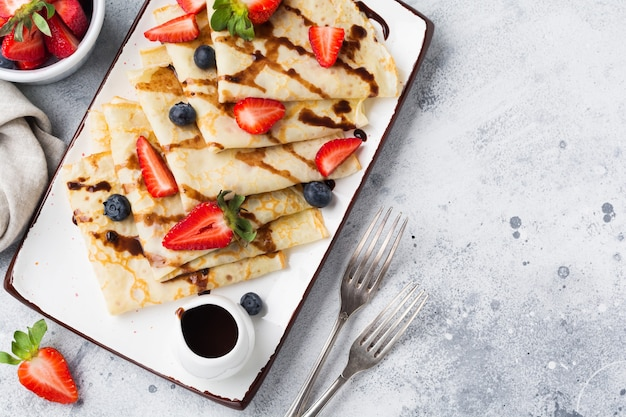 Zelfgemaakte pannenkoeken pannenkoeken met chocoladesaus, verse aardbeien en honing voor ontbijt in mooie witte keramische plaat. ruimte voor tekst of recept. bovenaanzicht.