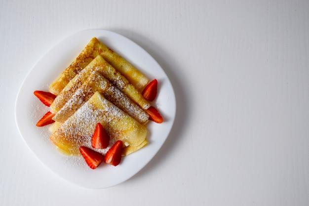 Zelfgemaakte pannenkoeken, smakelijke dunne pannenkoeken met aardbeien en poedersuiker op een witte plaat