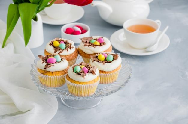 Zelfgemaakte pasen vanille cupcakes vogelnest met botercrème, chocolade en snoep eieren op een schotel. pasen leuk eten idee voor kinderen.