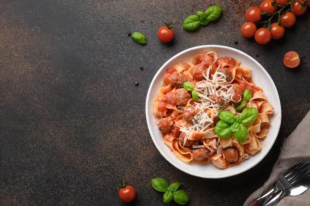 Zelfgemaakte pasta fettuccine met gehaktballen parmezaanse kaas tomaten basilicum op bruine achtergrond uitzicht van bovenaf