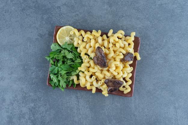 Zelfgemaakte pasta met gedroogd vlees op bruine plaat.