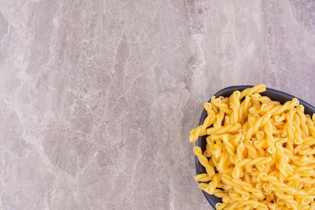 Zelfgemaakte pasta's in een zwarte ceramische kop op het marmer.