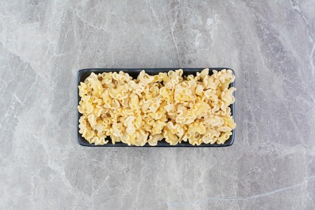 Zelfgemaakte pasta's in een zwarte keramische schotel