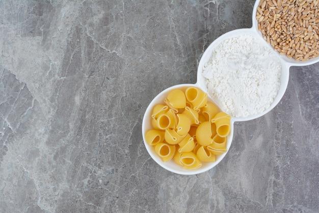 Zelfgemaakte pasta's met ingrediënten in witte ceramische kopjes