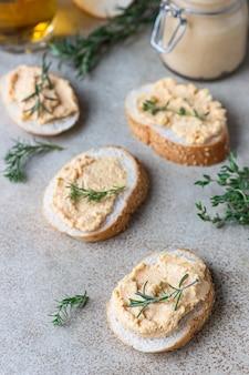 Zelfgemaakte paté of mousse in glazen pot met gesneden brood en kruiden