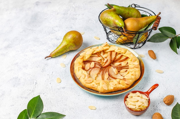 Zelfgemaakte peer galette taart met amandel bladeren en verse rijpe groene peren