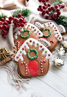 Zelfgemaakte peperkoek huizen dennentakken en bessen op witte houten tafel. flatlay, bovenaanzicht. kerst compositie