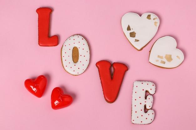 Zelfgemaakte peperkoek met letters liefde voor valentijnsdag gelegen op een roze achtergrond, bovenaanzicht, close-up