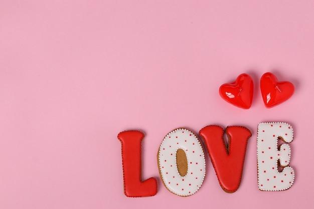 Zelfgemaakte peperkoek met letters liefde voor valentijnsdag gelegen op een roze achtergrond, bovenaanzicht, kopie ruimte